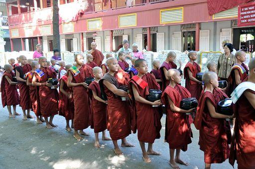 Mnisi przynoszą zebrane dary (na wspólny posiłek)