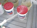 Washing off any dust or debris from the Grape Juice Bucket lids to prevent contamination.
