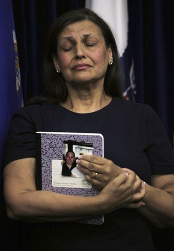 Judith Reiss, of Yardley, Pennsylvania, the mother of September 11, 2001 attack victim Joshua Reiss, holds his photo and closes her eyes as she waits to speak during a news conference held by family members of the attack victims at Camp Justice, the site of the U.S. war crimes tribunal compound, at Guantanamo Bay U.S. Naval Base, Cuba, July 16, 2009,